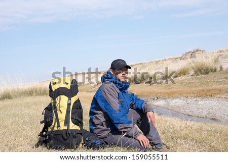 Hiker resting on the grass in autumn sunlight