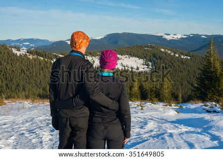 Hiker's couple stands in the winter mountains and looks into the valley  - stock photo