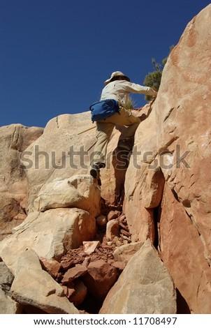 Hiker scrambling up rocks in Grand Canyon National Park, Arizona - stock photo