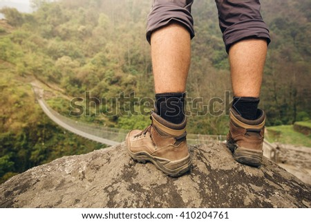 Hiker shoes on hiker legs standing above bridge