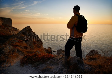Hiker silhouette on coastline at sunset - stock photo
