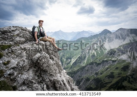 Hiker sits on a mountain cliff of the Allgau Alps - stock photo