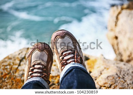 Hiker sits on edge of cliff overlooking water