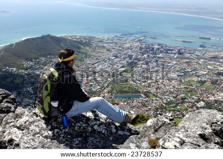 Hiker sitting on rock above Cape Town, South Africa - stock photo