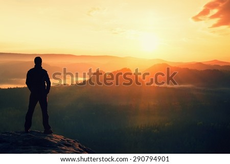 Hiker stand on the sharp corner of sandstone rock in rock empires park and watching over the misty and foggy morning valley to Sun.