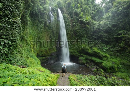 Hiker standing in front of huge Jungle waterfall surrounded by lush Jungle vegetation and flora in Lombok, Indonesia - stock photo