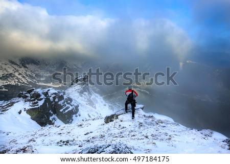 Hiker standing on a rock.Winter landscape.Climber on the snowy mountains.Travel inspiration and motivation, beautiful landscape.Active sport concept