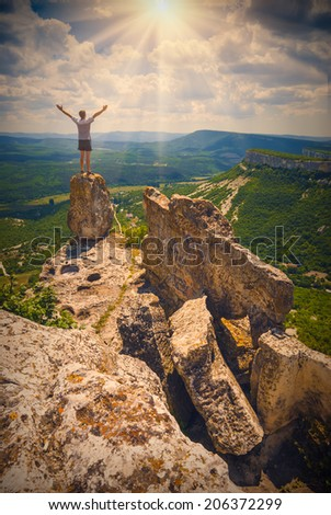 Hiker standing on top of a mountain with raised hands and enjoying sunrise  - stock photo