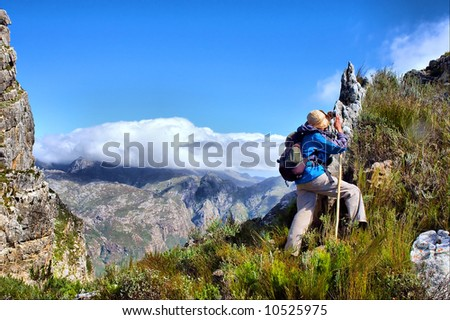 Hiker steps up - and awesome mountain landscape as a background. Shot on Pieke, Jonkershoek Nature Reserve, near Stellenbosch, Western Cape, South Africa.