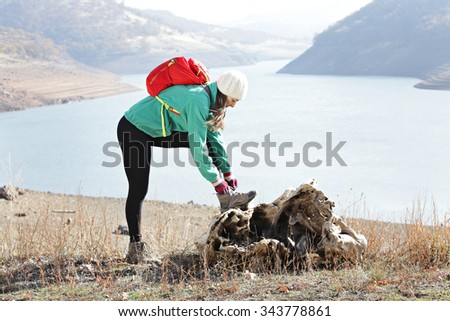 Hiker stopping to tie her shoe - stock photo