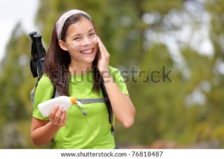 Hiker sunscreen. Woman hiking putting sun block lotion outdoors during summer hike holidays. Mixed race Caucasian Asian female model. - stock photo