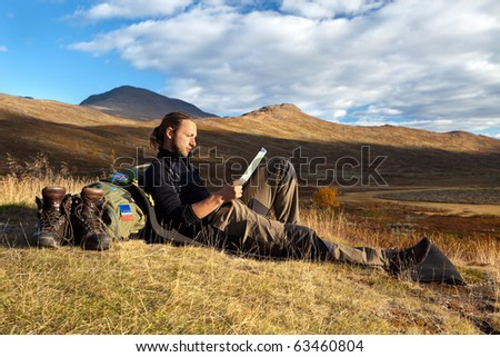 Hiker takes a break in the evening sun - stock photo