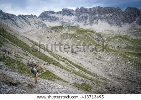 Hiker takes pictures on a mountain pass of the Allgau Alps - stock photo