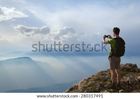 hiker taking photo of beautiful mountain landscape with mobile phone - stock photo