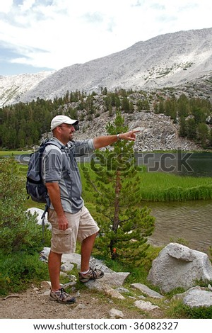 Hiker traverse the high country meadows of an alpine range - stock photo