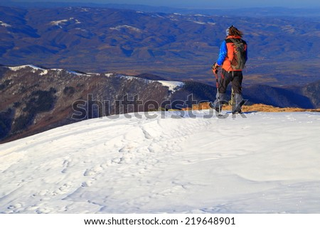 Hiker traverses a white snow field on the mountain - stock photo