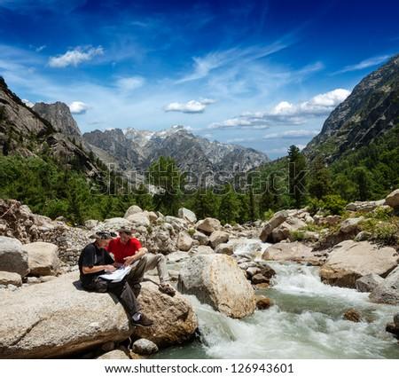 Hiker trekkers read a trekking map on trek in Himalayas mountains. Himachal Pradesh,India - stock photo