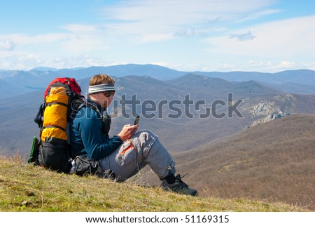 Hiker using mobile device in mountains - stock photo