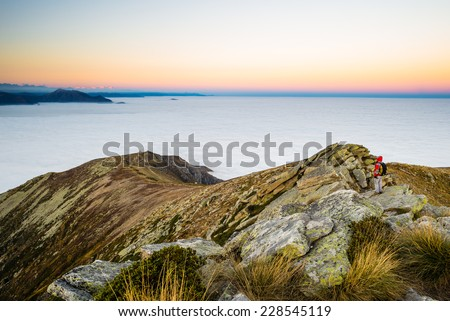 Hiker walking dawn on mountain ridge during twilight. Last sunlight on the horizon and high altitude alpine landscape with panoramic view of cloudy valley below. - stock photo