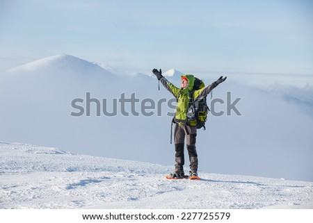 Hiker walking in sunny mountains in wintertime - stock photo