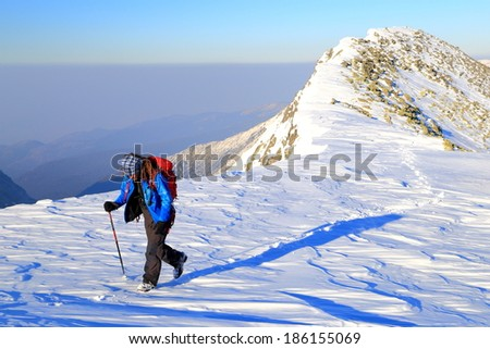 Hiker walking on snow covered mountain trail - stock photo