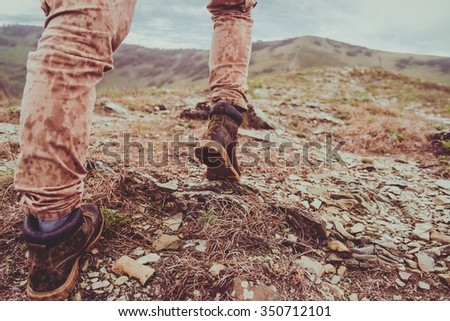 Hiker walking up on mountain in rainy weather. View of legs - stock photo