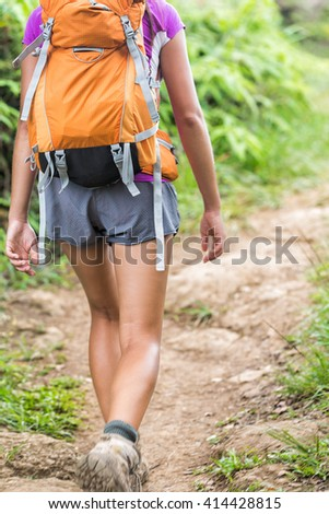 Hiker walking with orange backpack on hiking trail in forest nature on mountain path. Back view of shorts legs of trekking girl backpacking going up wearing boots on summer trip adventure activity. - stock photo