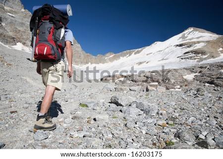Hiker walks on a mountain path, Gran Paradiso Park, Italy - stock photo