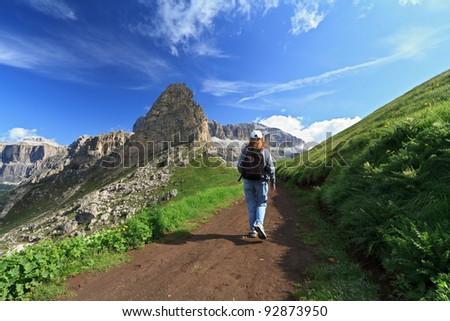 hiker walks on a path in Fassa Valley, Italian Dolomites - stock photo