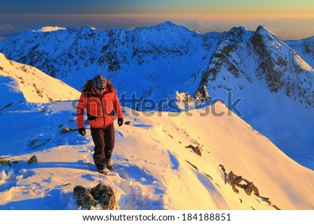 Hiker walks snow covered ridge at sunset - stock photo