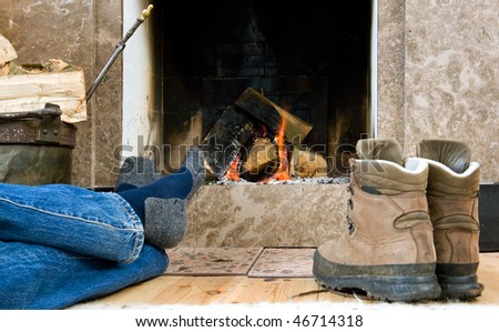 Hiker warming up and relaxing by a small fireplace - stock photo