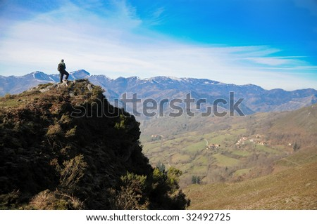 Hiker watching the landscape on a cliff in Asturias, Spain - stock photo