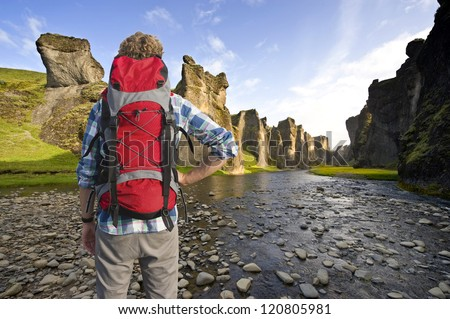 Hiker with a backpack admiring the trail throug an ancient Canyon in Hunkarbakkar, Iceland, where the different layers of volcanic branch pipes have created hard structures - stock photo