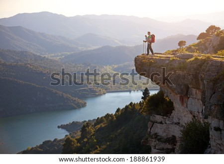 Hiker with baby relaxing on cliff and enjoying valley view. Siurana, Spain - stock photo