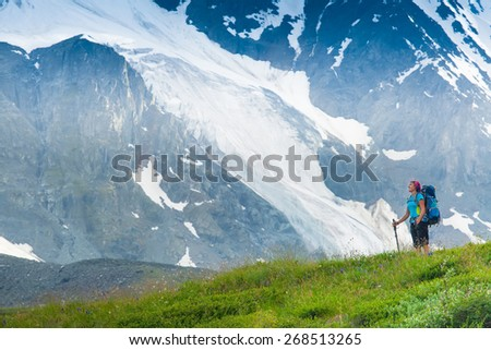 Hiker with backpack and trekking sticks to overcome difficulties in the mountains. Altai mountains, Russian Federation - stock photo