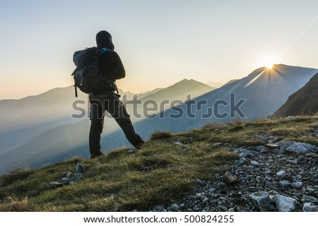 Hiker with backpack at sunrise in the mountains.