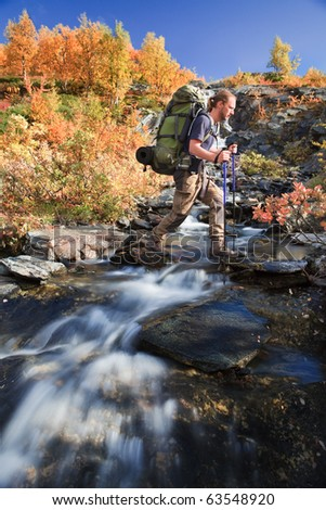Hiker with backpack crosses the creek - stock photo