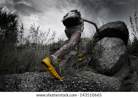 Hiker with backpack crossing rocky terrain - stock photo