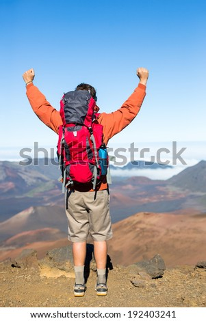 Hiker with backpack enjoying view from top of a mountain. Celebrating victory making it to the summit. Success and achievement concept. - stock photo
