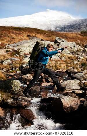 Hiker with backpack is jumping over a creek - stock photo