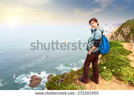Hiker with backpack on top of a mountain at sunset - stock photo