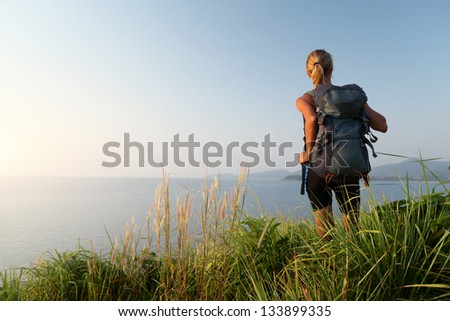 Hiker with backpack relaxing on a green meadow and enjoying sunset - stock photo