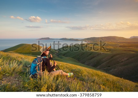 Hiker with backpack relaxing on a meadow and enjoying view. Woman backpacker sitting and enjoying the mountain landscape. - stock photo