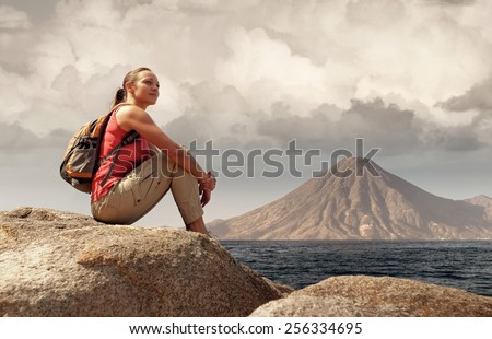 Hiker with backpack relaxing on a rock and enjoying the lake Atitlan. Guatemala. - stock photo