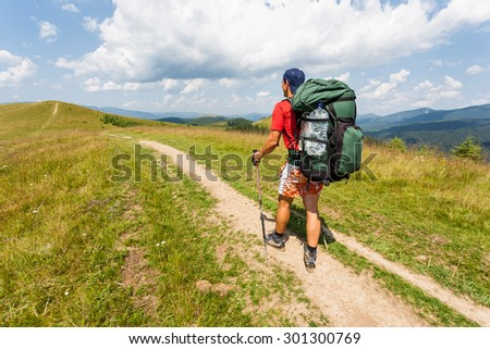 Hiker with backpack relaxing on top of a mountain and enjoying valley view.