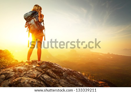 Hiker with backpack relaxing on top of a mountain and enjoying valley view during sunrise - stock photo