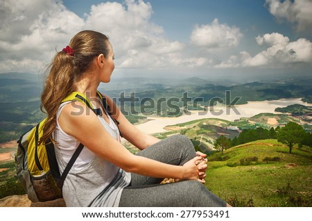 Hiker with backpack relaxing on top of the mountain.  Ecotourism concept image, with happy female hiker. - stock photo