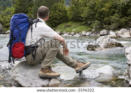 Hiker with backpack resting at a mountain river - stock photo