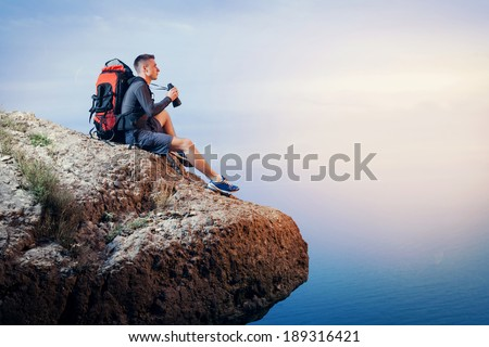 Hiker with backpack sitting on cliff of a mountain and looking through binoculars. - stock photo