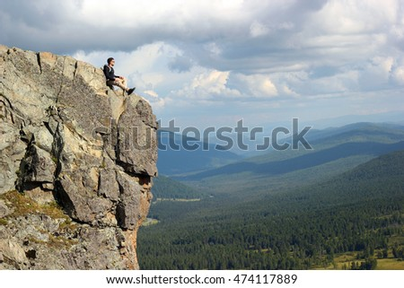 Hiker with backpack sitting on top off high rocks. Tourism concept.